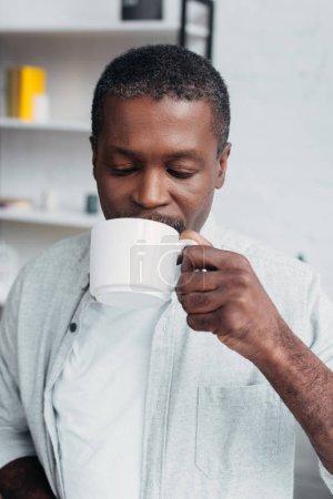 Photo pour Mature afro-américain de tenir la tasse blanche et boire du café - image libre de droit
