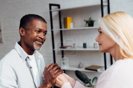 mature woman and african american man holding hands together