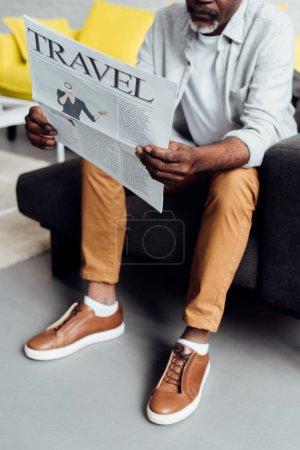 afro-américain assis sur le canapé et la lecture des journaux de voyage