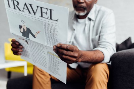 close up of african american man sitting on sofa and reading travel newspaper