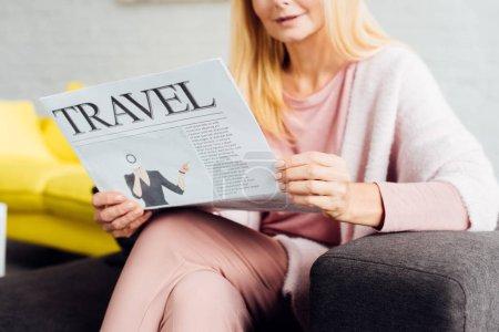 gros plan de femme d'âge mûr assis sur le canapé et la lecture des journaux de voyage