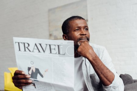 dreaming african american man reading travel newspaper