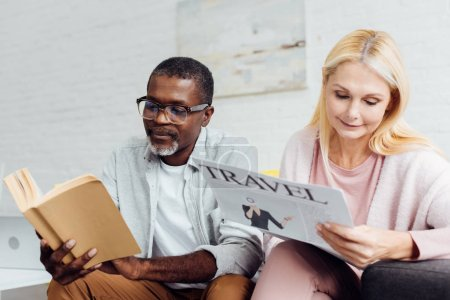 african american man in glasses reading book while mature woman reading travel newspaper