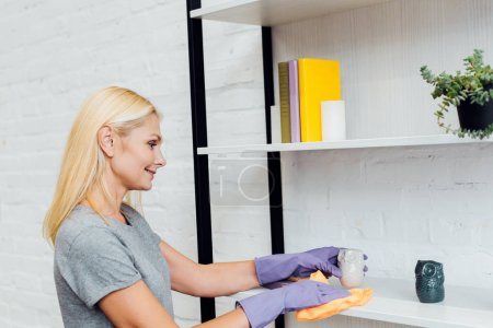 mature woman in gloves cleaning rack from dust