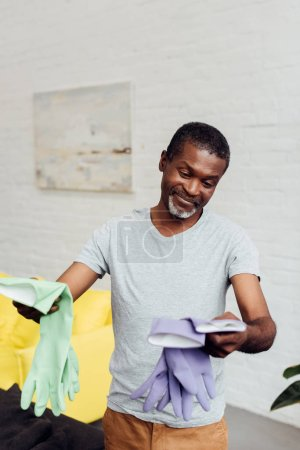 handsome smiling african american man holding rubber gloves