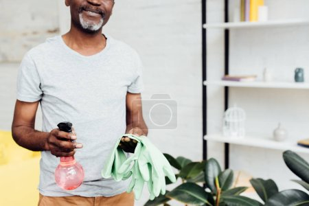 close up of african american man holding rubber gloves and spray