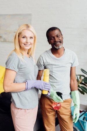 sourire de femme blonde et afro-américain dans des gants de caoutchouc tenue d'équipement ménager