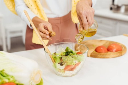 close up of female hands pouring oil in salad on table