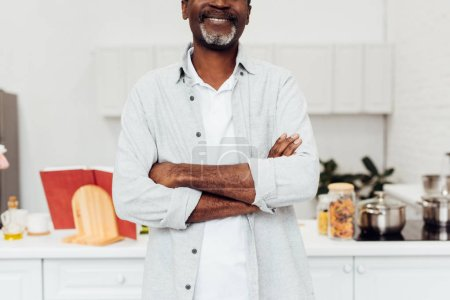 cropped view of african american man with arms crossed standing at kitchen