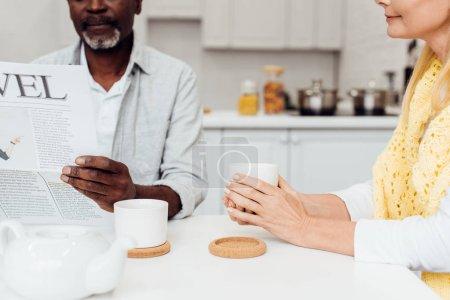 gros plan des afro-américain de lecture de journal tandis que femme buvant du thé