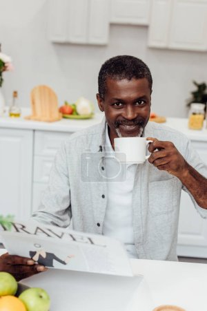 african american man drinking coffee and reading travel newspaper at kitchen