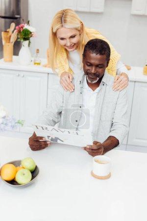 mature smiling woman embracing man while reading travel newspaper at kitchen