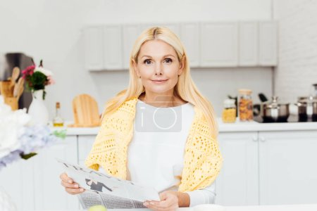 attractive blonde mature woman reading newspaper at kitchen