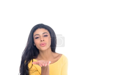 beautiful african american girl blowing kiss and looking at camera isolated on white