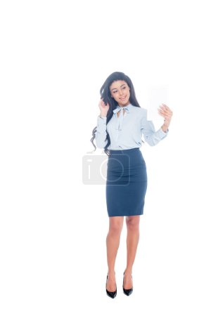 full length view of smiling young african american businesswoman using digital tablet isolated on white