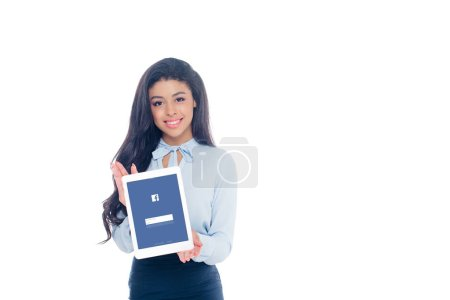 Photo for Beautiful young african american woman holding digital tablet with facebook application on screen and smiling at camera isolated on white - Royalty Free Image