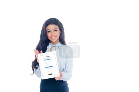 Photo for Beautiful young african american woman holding digital tablet with instagram application on screen and smiling at camera isolated on white - Royalty Free Image
