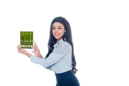 Photo pour Belle fille afro-américaine tenant une tablette numérique avec application médicale et souriant à la caméra isolé sur blanc - image libre de droit