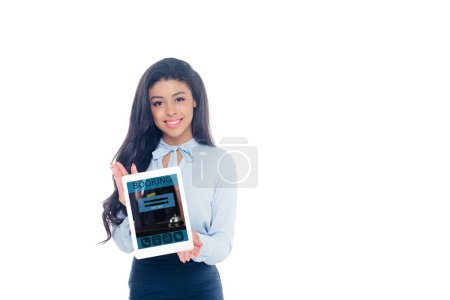 beautiful african american girl holding digital tablet with booking app and smiling at camera isolated on white
