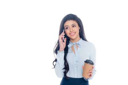 smiling young african american businesswoman holding coffee to go and talking by smartphone isolated on white