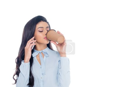 young african american businesswoman drinking coffee from paper cup and talking by smartphone isolated on white