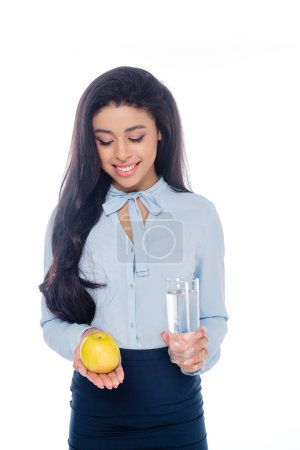 smiling young african american woman holding glass of water and apple isolated on white
