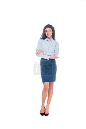 full length view of beautiful young african american woman standing with crossed arms and smiling at camera isolated on white