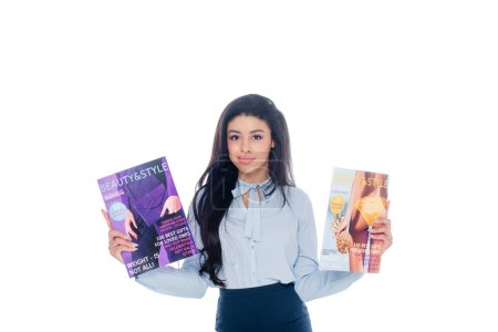 young african american woman holding beauty magazines and smiling at camera isolated on white