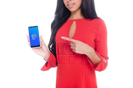 partial view of woman in red dress pointing at smartphone with shazam isolated on white