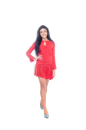 positive african american young woman in red dress posing with hand on waist isolated on white