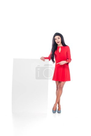 beautiful african american girl in red dress pointing at empty banner isolated on white