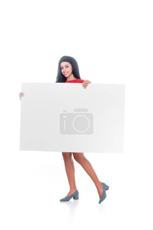 smiling african american girl in red dress showing empty banner isolated on white