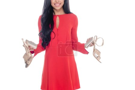 partial view of african american girl in red dress holding sandals with heels isolated on white