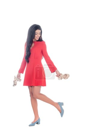 attractive african american girl in red dress holding sandals with heels isolated on white