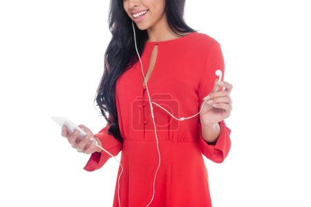 partial view of african american girl in red dress listening music in earphones with smartphone isolated on white
