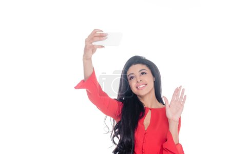 smiling african american in red dress taking selfie on smartphone and waving by hand isolated on white