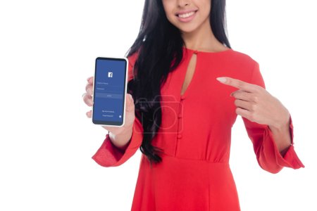 Photo for Partial view of woman in red dress pointing at smartphone with facebook isolated on white - Royalty Free Image