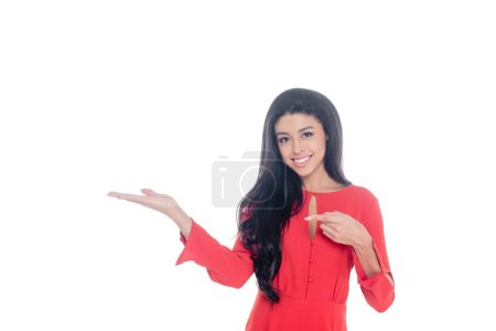 happy african american young woman in red dress pointing by finger isolated on white