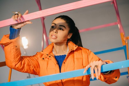 beautiful african american female model in orange winter jacket posing near colorful scaffold in studio with spotlight
