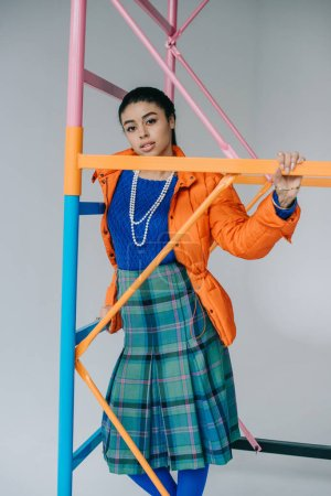 african american girl in orange winter jacket and checkered skirt posing near colorful scaffold in studio