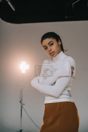 stylish african american female model in white turtle neck looking at camera in studio with spotlight