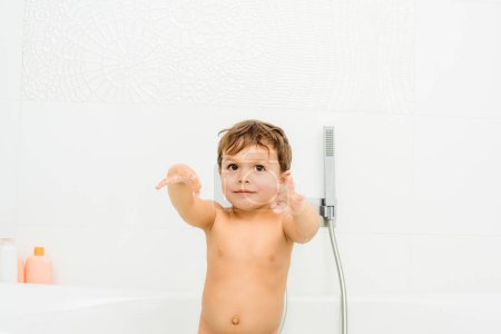 Small and cute boy gesturing in white bathroom