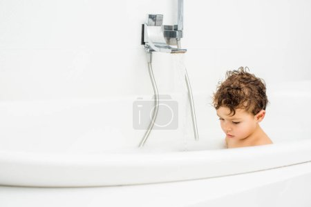 Toddler boy sitting in bathroom with running water