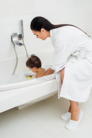 Mother in bathrobe washing son in bathroom