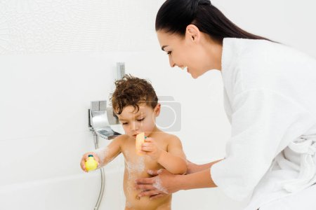 Smiling mother washing son in foam in white bathroom