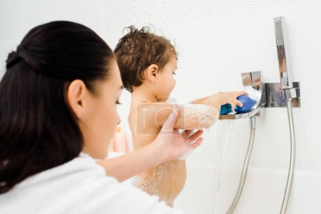 Mom holding hand of son playing in white bathroom