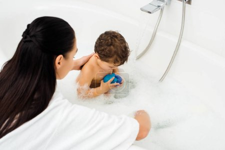 Woman washing toddler boy in white marble bathroom