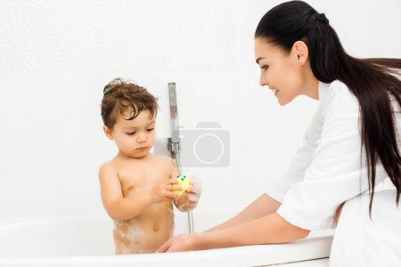 Mother washing son with yellow toy in white bathroom