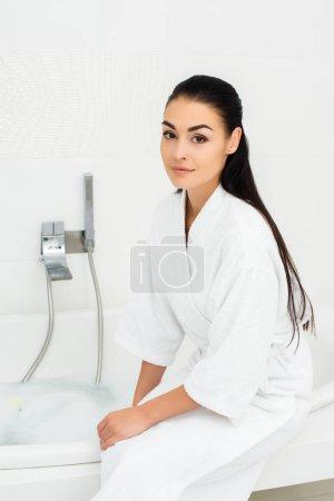 Photo pour Belle femme assise en peignoir blanc dans la salle de bain blanche - image libre de droit