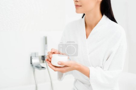Woman holding jar with cream in white bathrobe